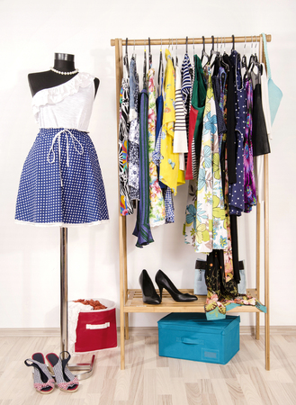 ruffle: Dressing closet with colorful clothes arranged on hangers and a summer outfit on a mannequin. Wardrobe with clothes and accessories. Tailors dummy wearing a blue floral skirt with a one shoulder white ruffle top. Stock Photo
