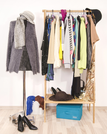 Wardrobe with clothes arranged on hangers and a winter outfit on a mannequin. Dressing closet with autumn clothes and accessories. Tailor's dummy wearing a fluffy grey sweater with scarf and hat.