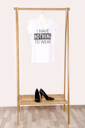 noting: Wardrobe with an empty rack with noting to wear t-shirt. Empty dressing closet with one t-shirt and a pair of black  high heel shoes.
