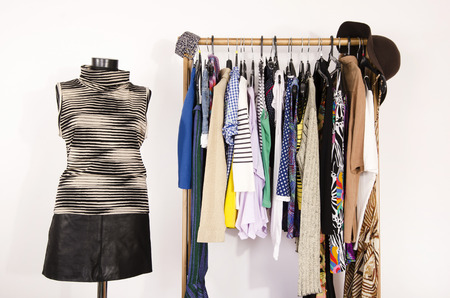 shirt: Dressing closet with colorful clothes arranged on hangers and an outfit on a mannequin. Wardrobe with clothes and accessories. Tailors dummy wearing a striped turtleneck and a black leather skirt.