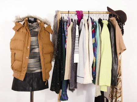 apparel: Wardrobe with clothes arranged on hangers and a winter outfit on a mannequin. Dressing closet with autumn clothes and accessories. Tailors dummy wearing a winter vest with leather skirt.