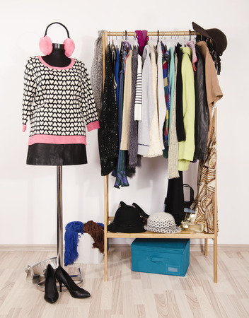 Wardrobe With Winter Clothes Arranged On Hangers And An Outfit On  Mannequin. Dressing Closet With