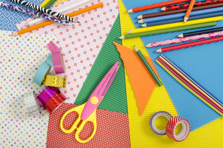 craft background: Arts and craft supplies. Color paper, pencils, different washi tapes, craft scissors.