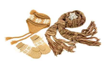 nicely: Brown wool scarf, a pair of mittens and a hat nicely arranged. Winter accessories isolated on white background.