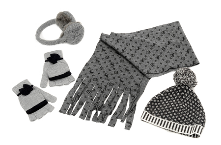 nicely: Winter accessories isolated on white background. Matching gray wool scarf, a pair of gloves, a hat and earmuffs nicely arranged.