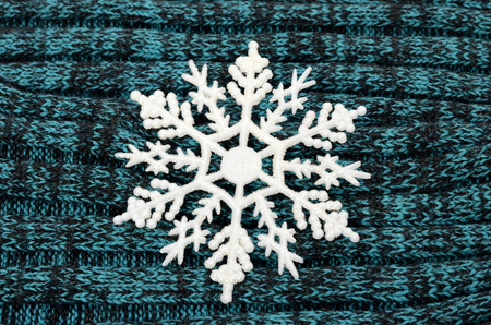 neckwear: Big white snowflake on gray and blue knitted wool background.