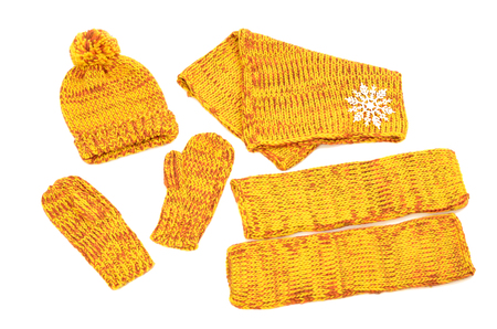 warmers: Winter accessories isolated on white background. Matching yellow neck wear, a pair of mittens, a hat and leg warmers nicely arranged.