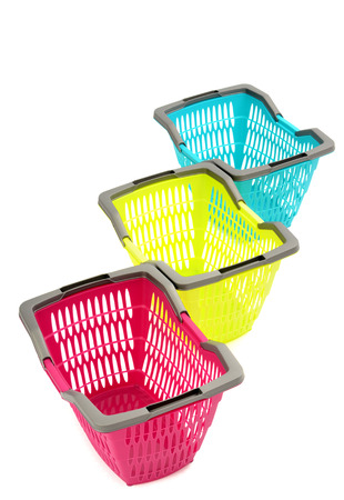 nicely: Blue, yellow and pink plastic shopping basket isolated on white. Three colorful empty market baskets nicely arranged in a row. Stock Photo