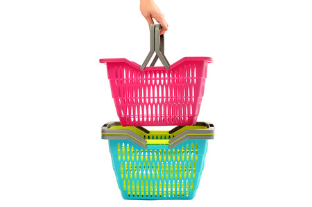 hand baskets: Woman hand taking a shopping basket from a pile. Pile of colorful empty plastic market baskets isolated on white.