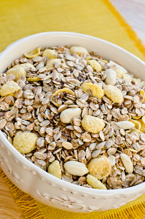 organic flax seed: White bowl with cereals for breakfast on a yellow table mat, close-up
