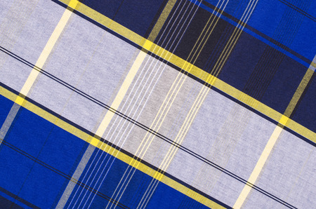 checked fabric: Scottish tartan pattern. Blue and white with yellow plaid print as background. Lines and square pattern. Scottish checked fabric.