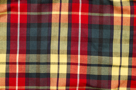 red plaid: Scottish tartan pattern. Red and purple plaid print as background. Colored lines and square pattern. Wrinkled material. Stock Photo