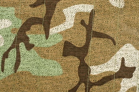 sewn: Camouflage pattern on fabric. Brown khaki military background sewn with green thread.