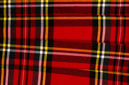 red plaid: Scottish tartan pattern. Red plaid print as background. Colored lines and square pattern. Scottish checked fabric folded. Stock Photo