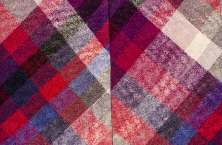 red plaid: Scottish tartan pattern. Red plaid print as background. Colored lines and square pattern. Scottish checked fabric with seam.