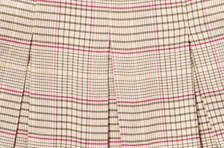 checked fabric: Brown and pink guncheck pattern. Tartan design as background. Checked fabric folded.