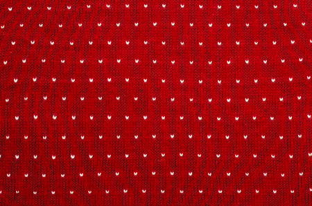 close knit: Close up on white and red heart dots woolen texture. Knit shapes pattern as a background.