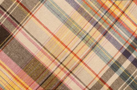 checked fabric: Scottish tartan pattern. Orange and green with yellow plaid print as background. Colored lines and square pattern. Scottish checked fabric.