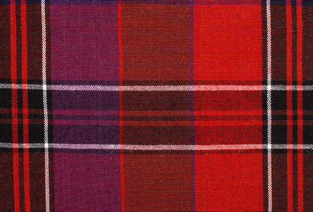 checked fabric: Scottish tartan pattern. Red and purple plaid print as background. Colored lines and square pattern. Scottish checked fabric.