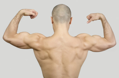 topless model: Topless man from the back raising his arms and fists. Fit bodybuilder showing his back muscles. Bald shaved man with big muscles, biceps, triceps and shoulders.