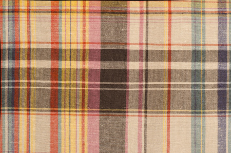 checked fabric: Scottish tartan pattern. Orange and brown with yellow plaid print as background. Colored lines and square pattern. Scottish checked fabric.