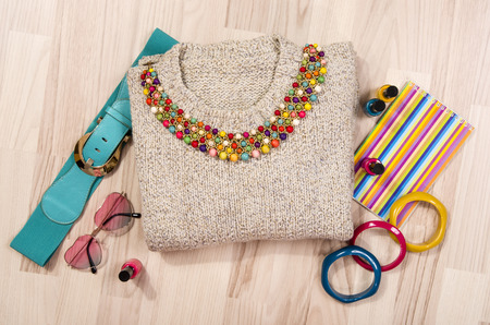 Winter sweater and accessories arranged on the floor. Woman colorful pink and blue accessories, hanger, belt, bracelets and nail polish.