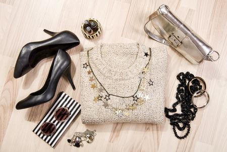 moda ropa: suéter de invierno y accesorios dispuestos en el suelo. Mujer negro con accesorios de oro y plata, tacones altos, pulseras, collares y esmalte de uñas.