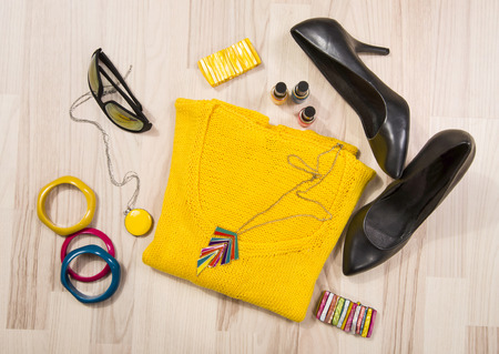 winter clothing: Winter sweater and accessories arranged on the floor. Woman colorful yellow accessories, high heels, sunglasses and nail polish. Stock Photo