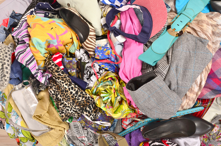 the thrown: Close up on a big pile of clothes and accessories thrown on the ground. Untidy cluttered wardrobe with colorful clothes and accessories.