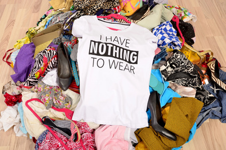 woman closet: Big pile of clothes thrown on the ground with a t-shirt saying nothing to wear. Close up on a untidy cluttered wardrobe with colorful clothes and accessories, many clothes and nothing to wear.