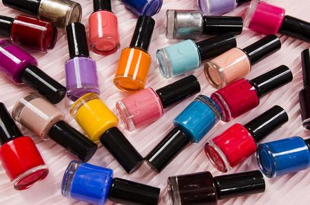 Pile de bouteilles colorées de vernis à ongles. Beaucoup de bouteilles de vernis à ongles couché sur fond rose. Banque d'images - 48041082