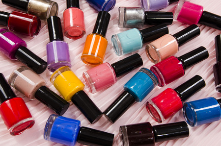 Stack of colorful bottles of nail polish. A lot of bottles of nail polish lying down on pink background.