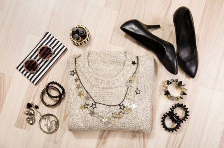Winter sweater and accessories arranged on the floor. Woman black with gold and silver accessories, high heels, bracelets, necklace and nail polish.