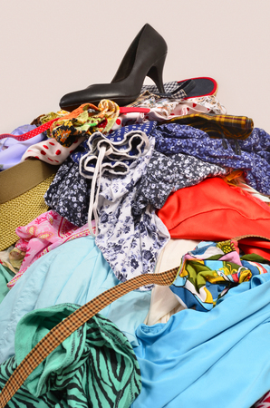 tienda de zapatos: Close up on a big pile of clothes and accessories thrown on the ground. Untidy cluttered wardrobe with colorful clothes and accessories.