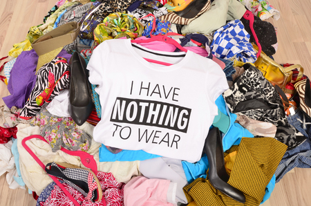 closet: Big pile of clothes thrown on the ground with a t-shirt saying nothing to wear. Close up on a untidy cluttered wardrobe with colorful clothes and accessories, many clothes and nothing to wear.