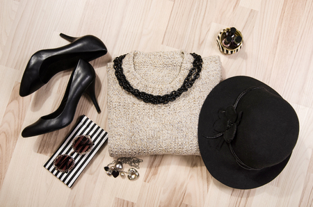 Winter sweater and accessories arranged on the floor. Woman black with silver accessories, high heels, hat, necklace and nail polish.