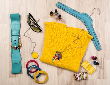 moda ropa: suéter de invierno y accesorios dispuestos en el suelo. Mujer accesorios de colores amarillo, gafas de sol y el esmalte de uñas.