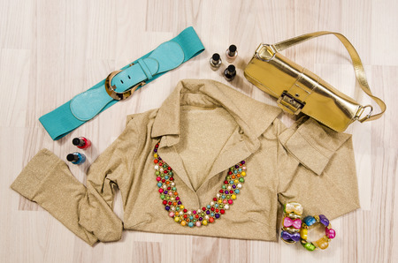 Gold blouse and accessories arranged on the floor. Woman gold and colorful accessories, blue belt. necklace, bracelets and nail polish.