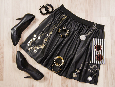 leather skirt: Black leather skirt and accessories arranged on the floor. Woman black and silver accessories, high heels shoes, necklace, bracelets and nail polish.