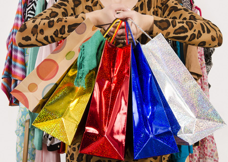 hanged: Close up on female hands holding many shopping bags. Unrecognizable woman holding colorful shopping bags with clothes hanged in the background. Girl shopping.