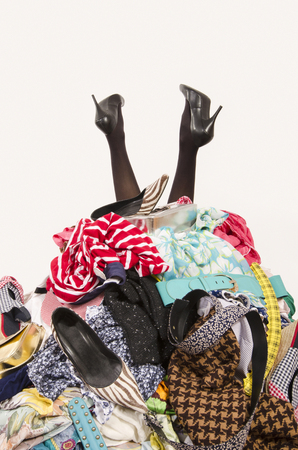 woman closet: Woman legs reaching out from a big pile of clothes and accessories. Woman buried under an untidy cluttered woman wardrobe. Woman in high heels needs help from to much shopping. Shopaholic girl. Stock Photo