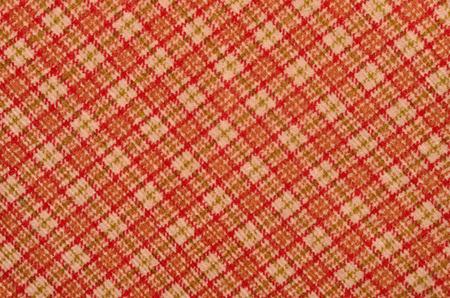 checked fabric: Orange with white plaid print as background. Scottish tartan pattern. Symmetric rhombus pattern. Checked fabric.