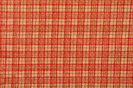 checked fabric: Orange with white plaid print as background. Scottish tartan pattern. Colored lines and square pattern. Checked fabric. Stock Photo