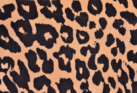 spotted fur: Black and orange leopard fur pattern. Spotted animal print as background.