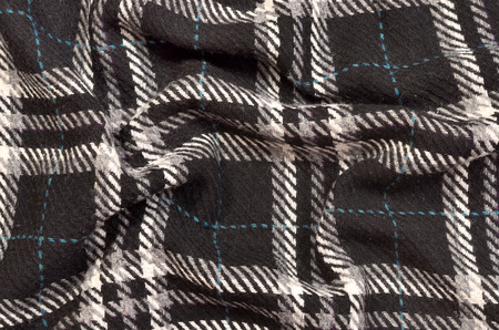 blue plaid: Tartan pattern on crumpled fabric. Black and white with blue plaid print as background.
