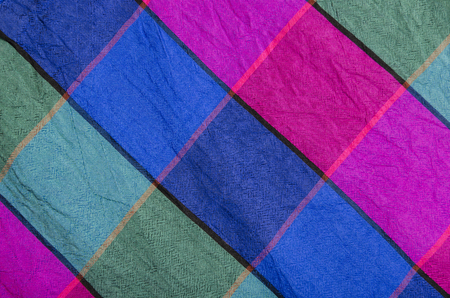 checked fabric: Green, green and magenta plaid print as background. Colored  square pattern. Checked fabric. Tartan pattern. Stock Photo