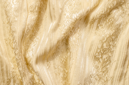 sparkly: Yellow gold textile pattern as a background.  Close up on crumpled sparkly gold material texture fabric. Stock Photo