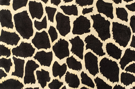 cow skin: Black and beige cow skin spots pattern.  Asymmetrical round shapes print on fabric as background.