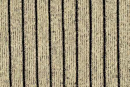 close knit: Close up on vertical knit woolen texture. Brown woven thread as a background.