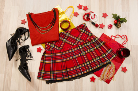 lied: Winter Christmas sweater and plaid skirt with accessories arranged on the floor. Woman red outfit with matching, necklace, bracelet and nail polish lied down. Stock Photo